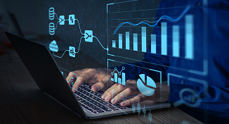 Image of a man using a laptop with digital graphs flowing out of the screen