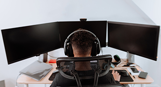 Image of person sat with 3 monitors